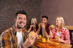 Les gens groupent manger des hamburgers d'aliments de préparation rapide se reposant au Tableau en bois en café Photographie stock libre de droits