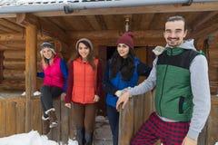 Les gens groupent près du cottage en bois de station de vacances de neige d'hiver de Chambre de montagne de pays Photo libre de droits