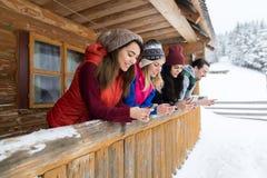 Les gens groupent utilisant le cottage en bois de station de sports d'hiver de neige d'hiver de maison de campagne de téléphone d Image stock