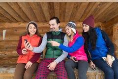 Les gens groupent utilisant le cottage en bois de station de sports d'hiver de neige d'hiver de maison de campagne de téléphone d Photographie stock libre de droits