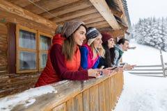 Les gens groupent utilisant le cottage en bois de station de sports d'hiver de neige d'hiver de maison de campagne de téléphone d Images stock