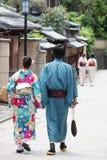 Les gens habillés avec les kimonos japonais traditionnels marchant dans le vieux secteur Japon de geisha de ville de Kyoto photographie stock