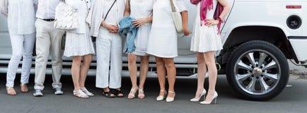 Les gens habillés dans la pose blanche à côté de la limousine Parties du corps, partie blanche image stock