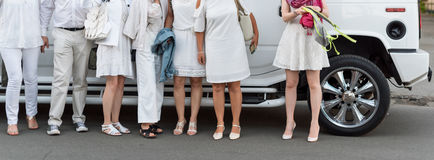 Les gens habillés dans la pose blanche à côté de la limousine Parties du corps, partie blanche images libres de droits