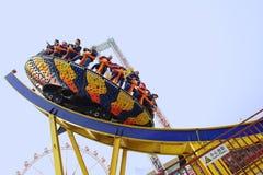 Les gens heureux jouent le chairoplane en parc d'attractions Photos libres de droits