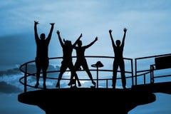 Les gens heureux sautent des silhouettes Photos libres de droits