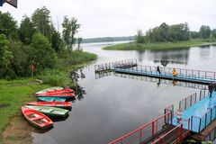 Les gens, hommes pêchent du ponton, du tablier, du pont sur le lac avec des canards et des bateaux sur le rivage à la récréation photo stock