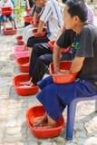 Les gens imbibent de leurs mains et pieds l'eau de fines herbes pour la SK Photos libres de droits