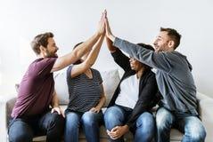 Les gens jointifs remettent ensemble sur le divan Photo stock