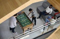 Les gens jouant appréciant la récréation le de jeu de football de Tableau de Foosball Photo stock