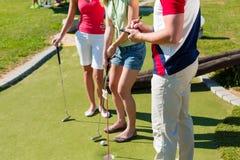 Les gens jouant au golf miniature à l'extérieur Images libres de droits