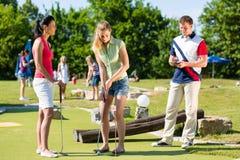 Les gens jouant au golf miniature à l'extérieur Photographie stock libre de droits