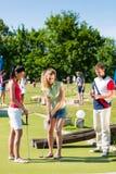 Les gens jouant au golf miniature à l'extérieur Photographie stock