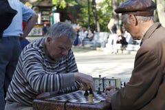 Les gens jouant des échecs en parc photos stock