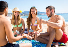 Les gens jouant des jeux de carte sur la plage Photos libres de droits