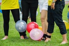 Les gens jouant des jeux sur le champ d'herbe verte dans le jour de sport du ` s de société Images stock