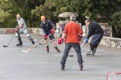Les gens jouant l'hockey de rue avec des bâtons et des rouleaux Photos stock