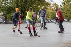 Les gens jouant l'hockey de rue avec des bâtons et des rouleaux Photographie stock libre de droits