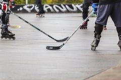 Les gens jouant l'hockey de rue avec des bâtons et des rouleaux Photo stock