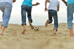 Les gens jouant le football sur une plage Photos libres de droits