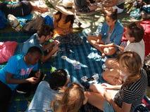 Les gens jouant le jeu de carte sur la couverture de pique-nique Images libres de droits