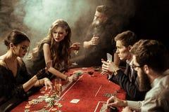 Les gens jouant le tisonnier ensemble dans le casino Images stock