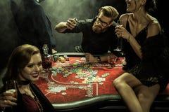 Les gens jouant le tisonnier ensemble dans le casino Images libres de droits