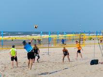 Les gens jouant le volleyball sur la plage ensoleillée Images stock