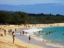 Les gens jouent dans les vagues et étayent à la grande plage Photographie stock libre de droits