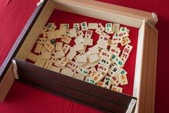 Les gens jouent le rummikub populaire de jeu de table de logique Image stock