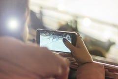 Les gens, l'amitié, le sport et les loisirs - amis heureux observant le jeu la personne prend un match d'hockey par le téléphone Photographie stock