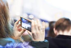 Les gens, l'amitié, le sport et les loisirs - amis heureux observant le jeu la personne prend un match d'hockey par le téléphone Photos stock