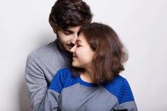 Les gens, l'amour et les relations Un couple sylish se tenant au-dessus du fond blanc Homme barbu à la mode utilisant le chandail Photo stock