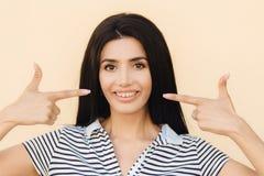 Les gens, la beauté et le concept de la publicité La jeune femme de brune avec le sourire doux, indique à la bouche avec le large photo libre de droits