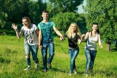 Les gens, la liberté, le bonheur, et le concept adolescent - le groupe d'amis heureux sortent et amusement sur un fond des arbres Photos libres de droits