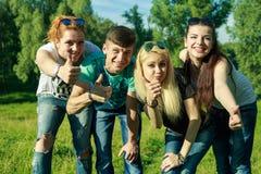 Les gens, la liberté, le bonheur, et le concept adolescent - le groupe d'amis heureux sortent et amusement sur un fond des arbres Image stock
