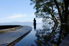 les gens, le ciel et les arbres ont inversé la réflexion dans l'eau image stock