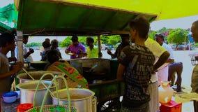 Les gens mangeant à un aliment extérieur typique de bord de mer calent sur Marina Beach, Chennai, banque de vidéos