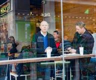 Les gens mangeant au café d'intérieur vu par la fenêtre de la rue Photographie stock