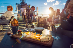 Les gens mangeant du fromage et buvant du vin au restaurant de dessus de toit au temps de coucher du soleil Photo stock