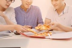 Les gens mangent des aliments de préparation rapide Mains d'amis prenant des tranches de pizza Photos stock