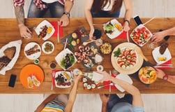 Les gens mangent l'alcool de boissons de repas au dîner de fête de table Photographie stock libre de droits