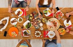 Les gens mangent les repas sains au dîner de fête de table Images libres de droits