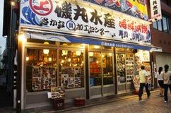 Les gens marchant à l'avant de restaurant local de fruits de mer japonais à photographie stock libre de droits