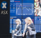 Les gens marchant après le conseil de visualisation électronique de Sydney Exchange Square Photographie stock libre de droits