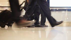 Les gens marchant avec le bagage dans l'aéroport international, se ferment vers le haut du tir des jambes et des chaussures Photos libres de droits