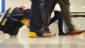 Les gens marchant avec le bagage dans l'aéroport international, se ferment vers le haut du tir des jambes et des chaussures Image libre de droits
