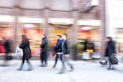 Les gens marchant contre la fenêtre de boutique, effet de bourdonnement, tache floue de mouvement Image stock