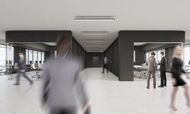 Les gens marchant dans le bureau avec le noir et les murs de verre Images stock