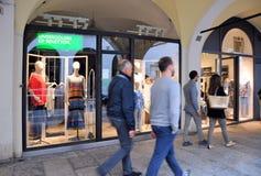 Les gens marchant devant des fenêtres de boutique et faisant des emplettes dans le portique central du XVIème siècle Photographie stock libre de droits